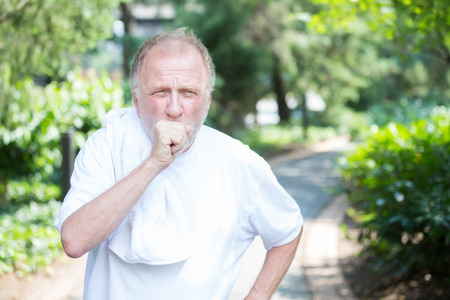 Closeup portrait, senior guy holding towel, very tired, exhausted from over exertion, coughing catching breath, isolated outdoors outside green trees background Standard-Bild