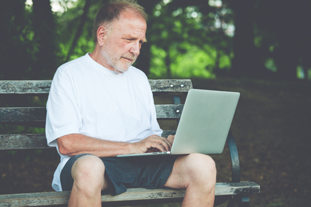 Closeup portrait, senior mature man in white shirt typing away, browsing digital computer laptop, isolated background of sunny outdoor, green trees nature background Banco de Imagens