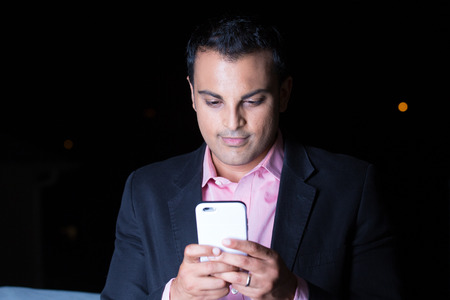 Closeup portrait, young man in black blazer, pink shirt using cell phone, texting at night, isolated outdoors black background Banco de Imagens