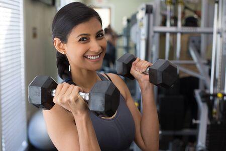 Close-upportret, jong aantrekkelijk vrouwen opheffend gewicht in gymnastiek, binnen met materiaal op de achtergrond