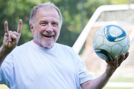 Het close-upportret, de bejaarde die voetbalbal en het pronken met hoornen steunen ondertekent met handen, de geïsoleerde post van het voetbaldoel in openlucht achtergrond
