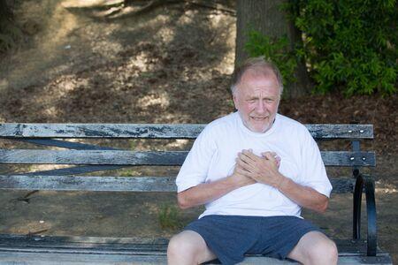 Close-upportret, oude mens clutching borst, die hartpijn hebben, zittend op bank, in openlucht geïsoleerde, groene bomenachtergrond. Myocardiaal infarct, breuk van het aorta-aneurysma