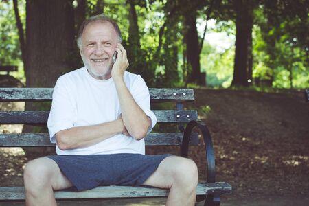 Close-upportret, oudere, gelukkige extatische mensenzitting op bank die op celtelefoon spreken, geïsoleerde in openlucht achtergrond