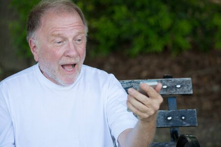 Het close-upportret van de gewaagde bejaarde in wit die overhemd, bij het controleren van smartphone wordt geschokt, tekstbericht, gezet op een bank, geïsoleerde openluchtachtergrond verzendt. Stockfoto