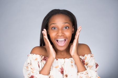 Closeup portrait of happy cute young beautiful woman taken aback in disbelief hands on face isolated gray background. Positive human emotion, facial expression, feeling, reaction