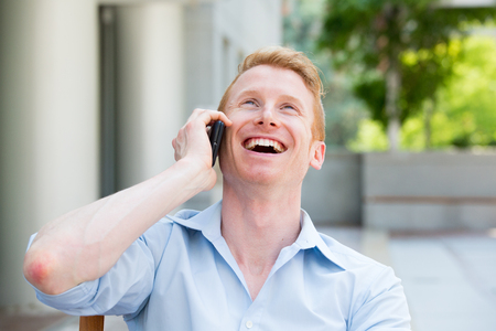 Closeup portrait, young happy ecstatic man with wide open mouth talking on cell phone, isolated outdoors background Banco de Imagens