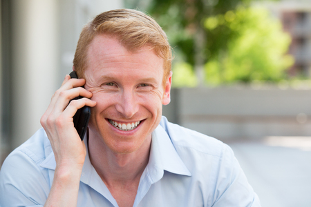 Closeup portrait, young happy ecstatic man with grinning mouth, talking on cell phone, isolated outdoors background
