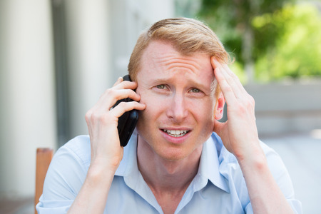 Closeup portrait, worried young man in blue shirt talking on phone to someone, looking gloomy, isolated outdoors outside background