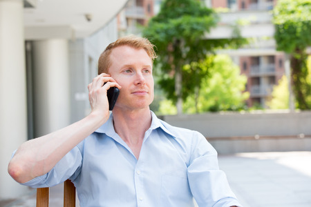 Closeup portrait, young man listening to conversation on cell phone, isolated outdoors outside background Banco de Imagens
