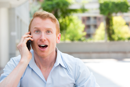 closeup portrait, young happy ecstatic man with wide open mouth talking on cell phone, isolated outdoors background