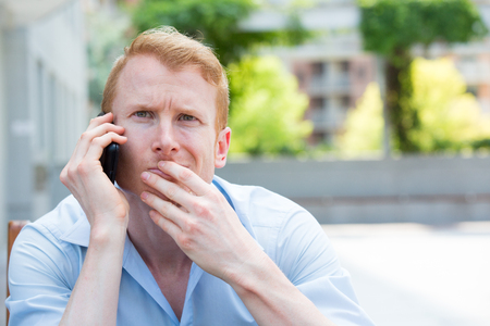 Closeup portrait, young man perplexed, baffled, befuddled, bewildered by someone talking on his mobile phone, isolated outdoors background