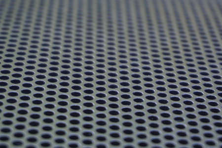 Photo of a loudspeaker grill as a background. Selective focus through the middle.