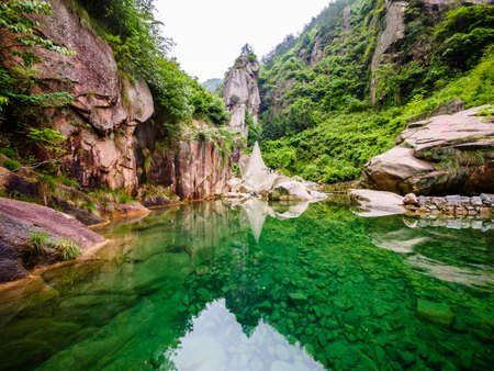 Huihang Ancient Trail Hiking Tour.  lake in mountains between Anhui and Zhejiang with the reflection of big rocks, China
