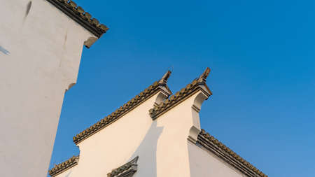 horse head wall with black tiles and bricks on wall top of traditional Chinese Anhui architecture used for separation of individual private courtyard and in case of fire, with pure blue sky background.