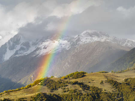 Beautiful mountain rainbow with snow mountains background, Sichuan, China.