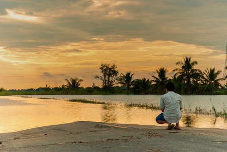 city park boat house: Men sit watching the flood, Thailand floods, Natural Disaster,