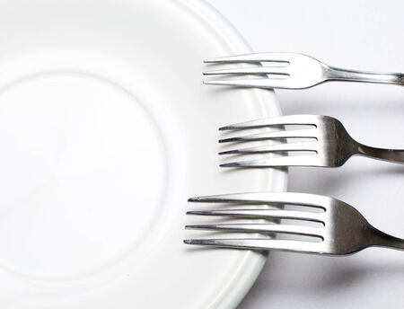 White plate, fork  on light background  photo