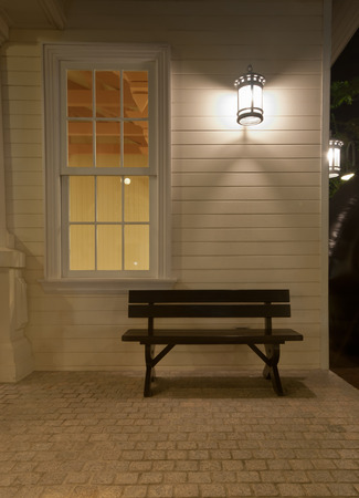 chair in front house at night photo