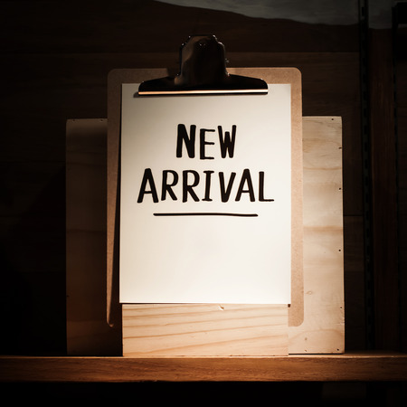 new arrival: New arrival words written on clipboard