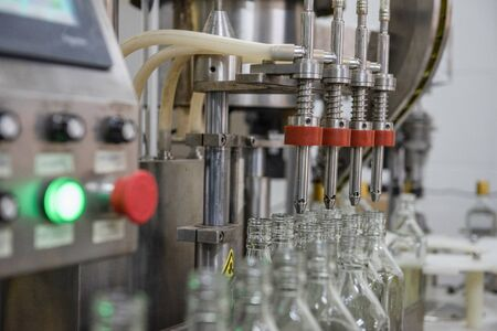 close up machines filling fresh water to glass bottles Stock Photo