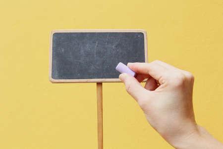 Mano que escribe en la pizarra, con un muro de color amarillo como fondo