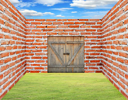 Brick wall with wooden door with gras and sky Stock Photo