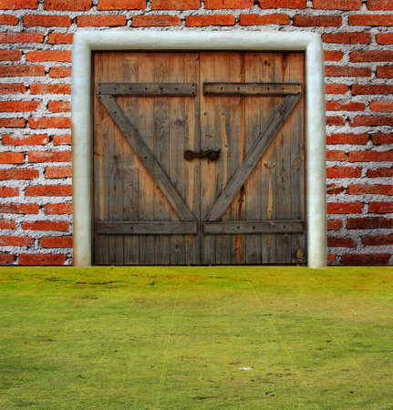 Brick wall with door on grass ground