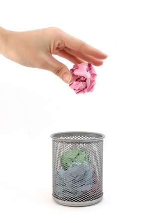 A hand placing paper in trash can on white background photo