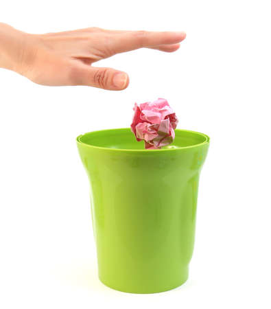 hand basket: A hand placing paper in plastic bin on white background Stock Photo