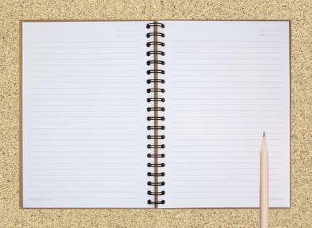 Nota Libro abierto sobre fondo tablero de corcho con un l�piz