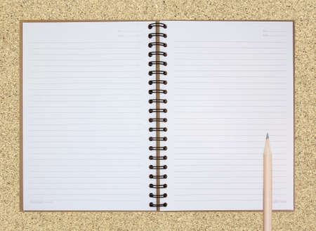 Opened note book on cork board background with pencil