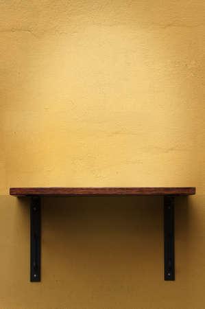 Wood shelf on yellow wall