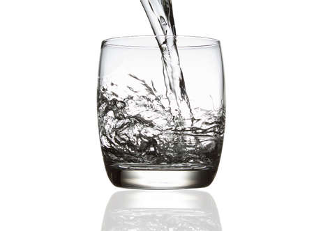 Pouring water into the glass, isolated on white
