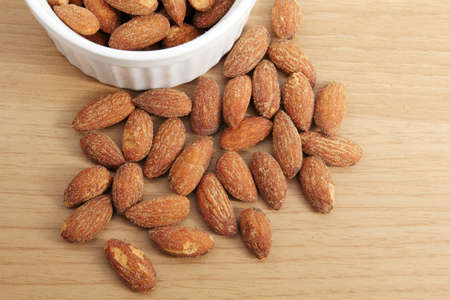 Roasted almonds with salt on wood background