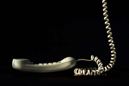 Telephone with cord isolated on black