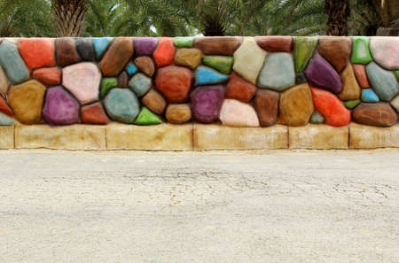Colorful stone wall background on concrete street