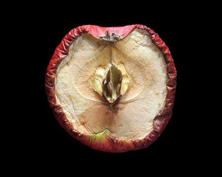 A rotten apple cut in half, dramatic lightning.