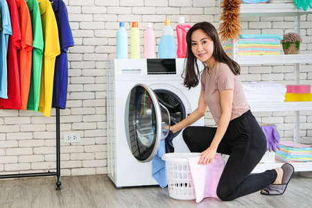 A smiling and cute Asian woman carrying a laundry basket and posing beside the washing machine. Picking up clothes in the washing machine. There are empty shelves and clothes racks.