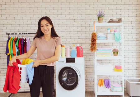 An Asian woman walks in a laundry basket. There are many colors in the basket. Looking at cleanliness Happy and smiling, inside the house there are empty floors Washing machine