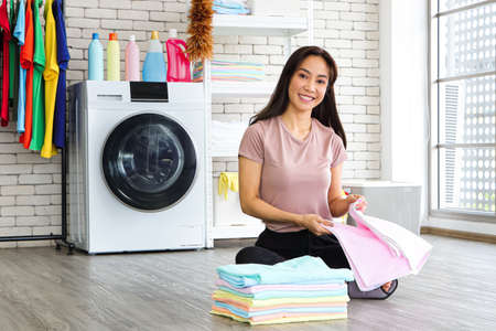 Asian woman sitting in the laundry room She picked up the folded laundry and checked the cleanliness after the washing machine finished. Smile and happiness Reklamní fotografie