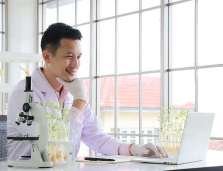 Asian researchers in white coats The concept of working in a scientific laboratory Using a laptop to find information And write down in the test results book Or making a report in a science laboratory