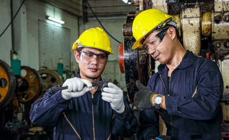 Asian engineer Safety uniforms use vernier calipers to measure workpieces. Machine control concept. Check the quality and design of metal parts working in industrial plants and manufacturing processes Stock Photo