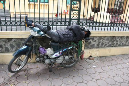 get tired: Sleeping man on his motobike on the street. Rest on motobike in lazy day. Hanoi, Vietnam.