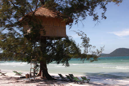 ron: Tree house from reed on green tree. Beach with white sand and turquoise sea. Koh Ron island. Cambodia.