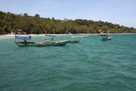 ron: Trip wooden boats in pristine turquoise water near tropical island. Cambodia. Koh Ron island.