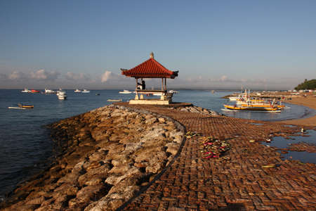 peacefull: View of blue sea, boats and stone pier with pavilion and rest of flowers and coconut offering in Bali. Stock Photo