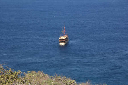 masts: White ship with two masts in bright blue sea near bank of Bali.