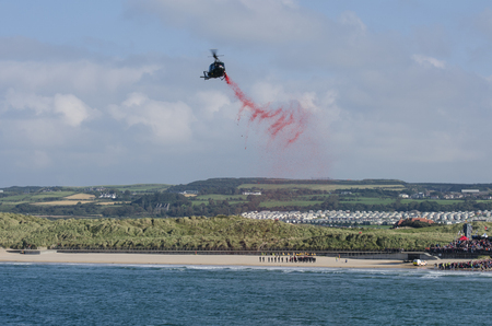 legion: The final part of Portrush Airshow:- A Helicopter drops poppies over the Royal Brittish Legion Standard Bearers on Esat Strand Portrush as part of an Act of Commeration for service men  women who lost their lives in various conflicts around the world.
