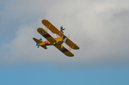 In The Sky, Portrush, Northern Ireland - August 31, 2013:- An Unknown male is Wing Walking on an old Bi Plane at the Airshow Portrush