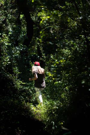 Woman walking on a path in a strange dark green forest. Woodland walk.